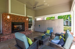One Bedroom Apartments for Rent in Conroe, TX - Covered Outdoor Seating Area with lit Fireplace & Package Hub